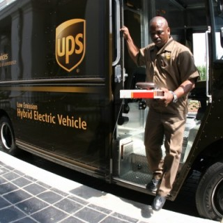 UPS employee in uniform with package, in front of truck with logo