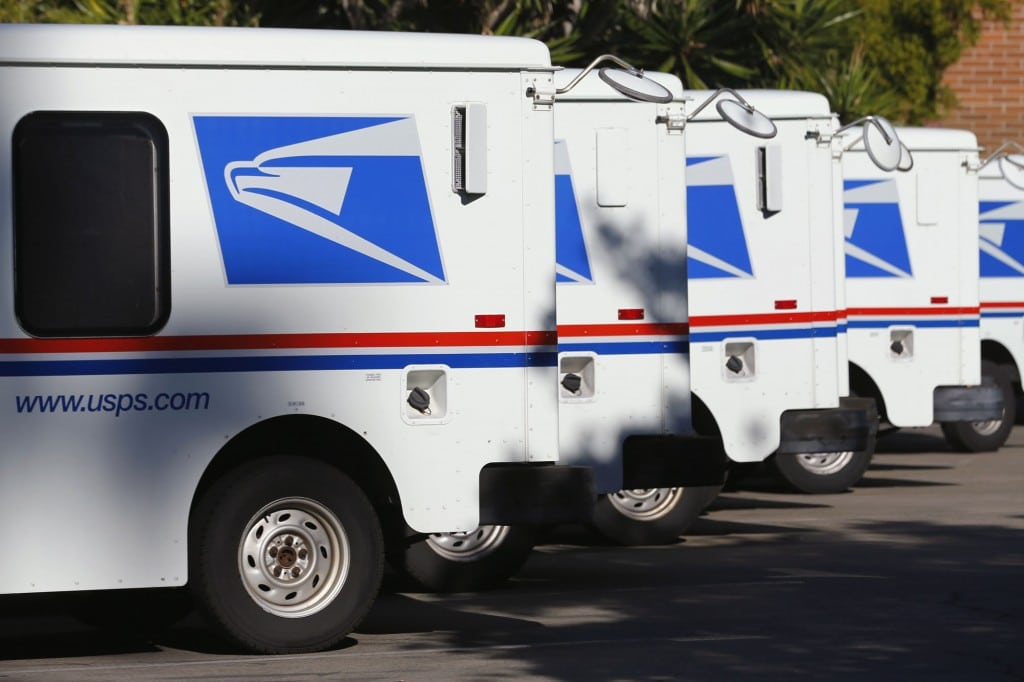 fleet of USPS trucks parked