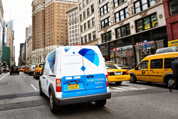 white and blue branded Google Package truck driving through urban setting
