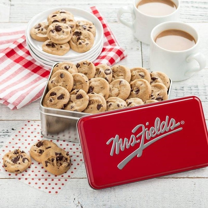 mrs fields cookies in a tin with logo and around it on white plates