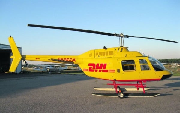 Helicopter in DHL brand colors, yellow and red, in heliport