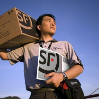 Asian male shipping company employee carrying packages