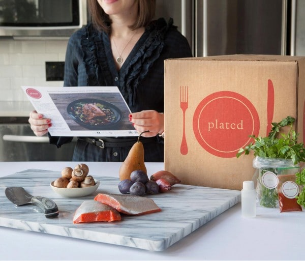 woman receiving snack box package via Plated app subscription service