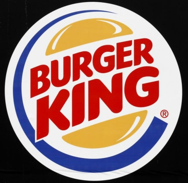 burger king company logo, with red lettering, black background and burger bun